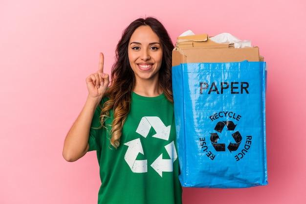 Junge mexikanische frau recycling karton isoliert auf rosa hintergrund zeigt nummer eins mit dem finger.