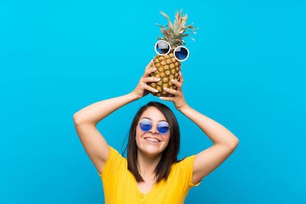 Junge mexikanische frau über dem lokalisierten blau, das eine ananas mit sonnenbrille hält