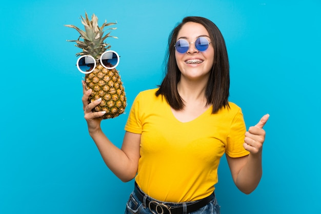 Junge mexikanische frau über dem lokalisierten blauen hintergrund, der eine ananas mit sonnenbrille hält