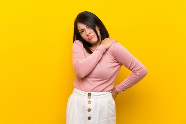 Junge mexikanische frau über dem lokalisierten gelb, das unter den schmerz in der schulter leidet, weil sie sich bemüht hat