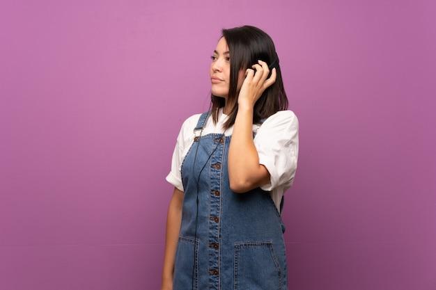 Junge mexikanische frau über lokalisiertem hören musik mit kopfhörern