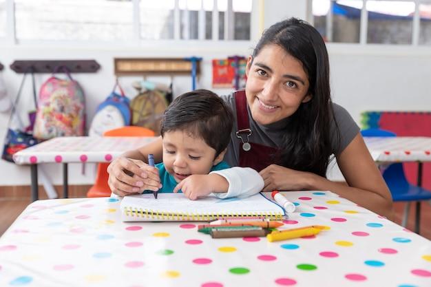 Junge mexikanische lehrerin und kind im kindergartenklassenzimmer, vorschulbildungskonzept