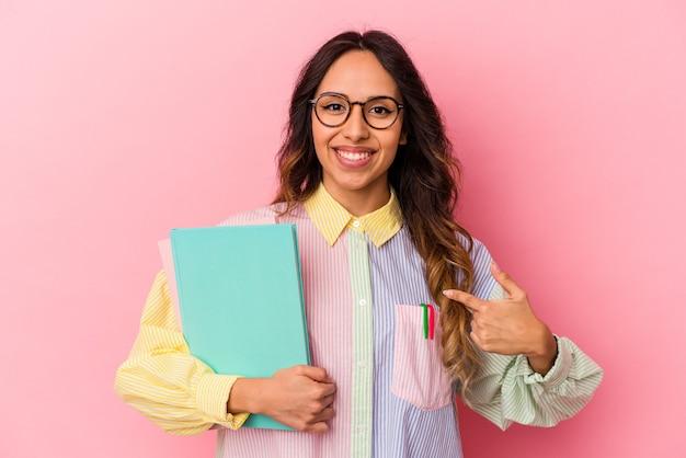 Junge mexikanische studentin einzeln auf rosafarbenem hintergrund, die mit der hand auf einen hemdkopierraum zeigt, stolz und selbstbewusst