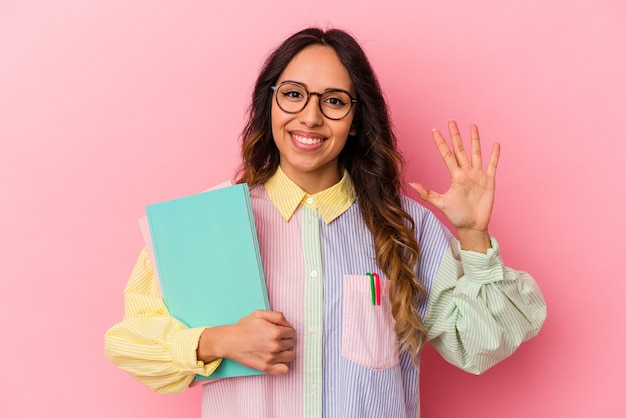 Junge mexikanische studentin isoliert auf rosa hintergrund lächelnd fröhlich mit nummer fünf mit den fingern.