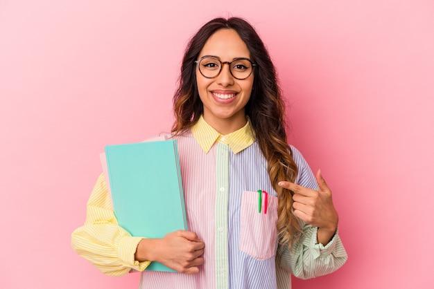 Junge mexikanische studentin isoliert auf rosa hintergrund lächelt und zeigt beiseite und zeigt etwas an der leerstelle.