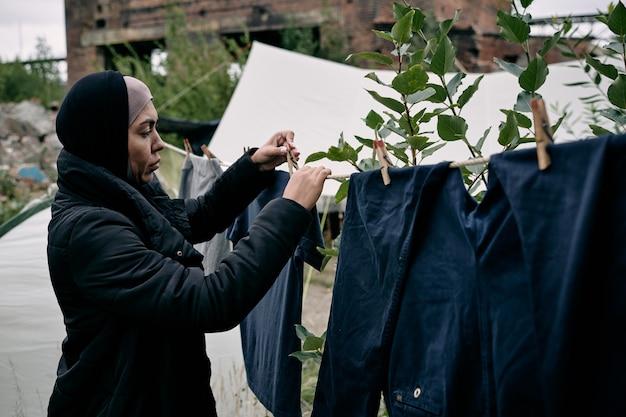 Junge migrantin, die saubere kleidung am seil hängt