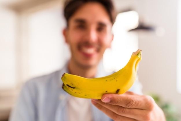Junge mischlinge, die banane in einer küche seines hauses essen