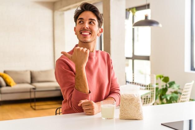 Junge mischlinge, die haferflocken und milch zum frühstück in seiner küche essen, zeigen mit dem daumen weg, lachen und sorglos.