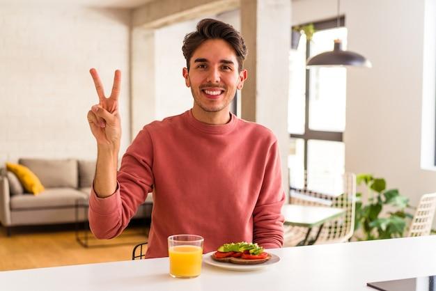 Junge mischlinge, die in seiner küche frühstücken und die nummer zwei mit den fingern zeigen.