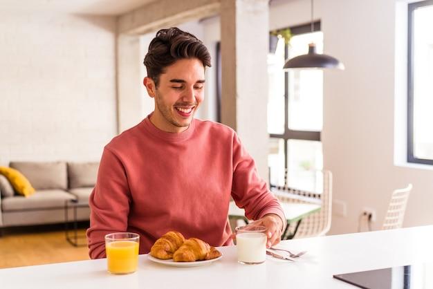 Junge mischlinge, die morgens in einer küche ein croissant essen