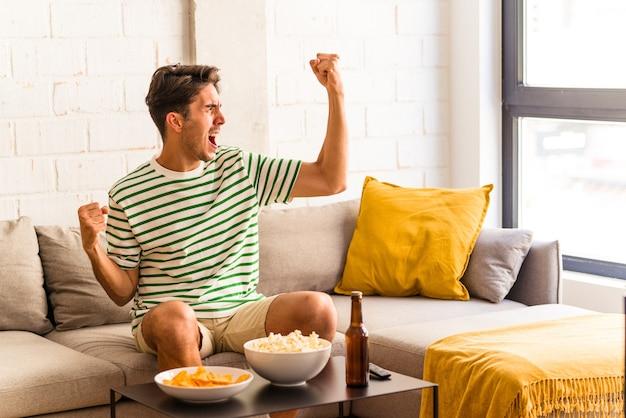 Junge mischlinge, die popcorn essen, sitzen auf dem sofa und heben die faust nach einem sieg, gewinnerkonzept.