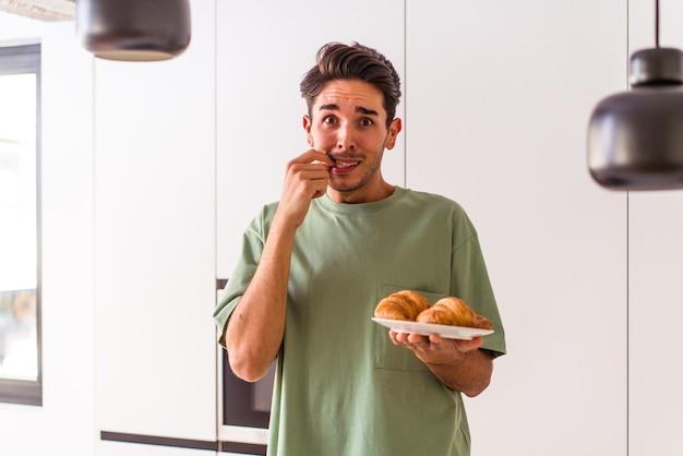 Junge mischlinge essen croissant in einer küche am morgen beißende fingernägel, nervös und sehr ängstlich.