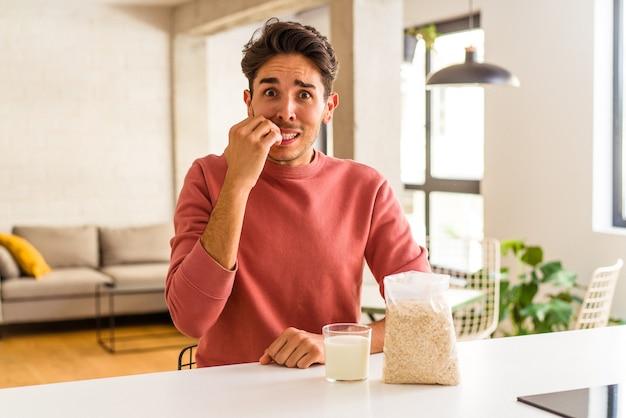 Junge mischlinge essen haferflocken und milch zum frühstück in seiner küche beißende fingernägel, nervös und sehr ängstlich.