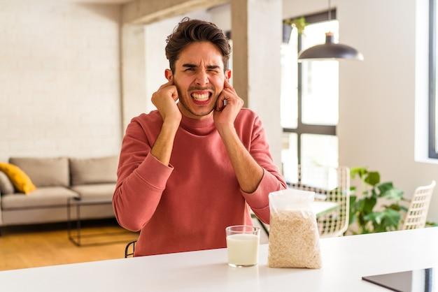 Junge mischlinge essen haferflocken und milch zum frühstück in seiner küche und bedecken die ohren mit den händen.