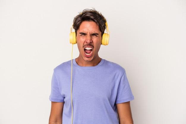 Junge mischlinge hören musik einzeln auf blauem hintergrund und schreien sehr wütend und aggressiv.