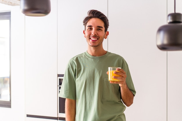 Junge mischlinge trinken orangensaft in seiner küche glücklich, lächelnd und fröhlich.