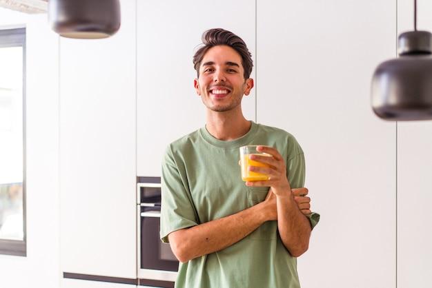 Junge mischlinge trinken orangensaft in seiner küche lachen und spaß haben.