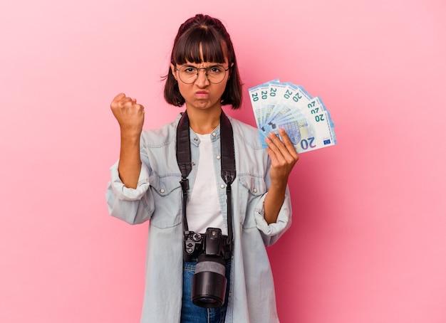 Junge mischlingsfotografin, die rechnungen einzeln auf rosafarbenem hintergrund hält und die faust zur kamera zeigt, aggressiver gesichtsausdruck.