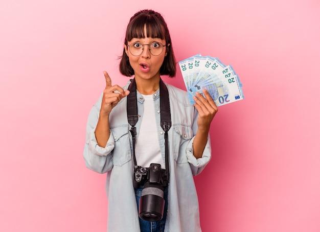 Junge mischlingsfotografin, die rechnungen einzeln auf rosafarbenem hintergrund hält und eine idee, ein inspirationskonzept hat.