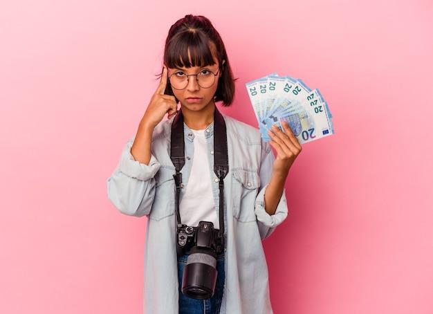 Junge mischlingsfotografin, die rechnungen einzeln auf rosafarbenem hintergrund hält und mit dem finger auf den tempel zeigt, denkt, konzentriert sich auf eine aufgabe.