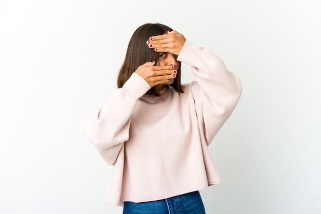 Junge mischlingsfrau blinzelt durch finger, verlegenes bedeckendes gesicht.