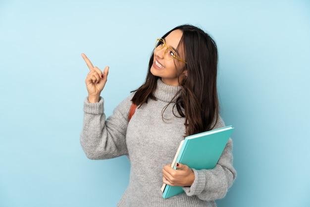 Junge mischlingsfrau, die auf blaue wand zur schule geht, zeigt mit dem zeigefinger eine große idee