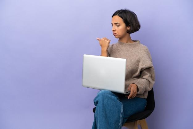 Junge mischlingsfrau, die auf einem stuhl mit laptop sitzt, lokalisiert auf violettem hintergrund unglücklich und auf die seite zeigend