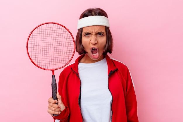 Junge mischlingsfrau, die badminton spielt, isoliert auf rosa wand, die sehr wütend und aggressiv schreit.