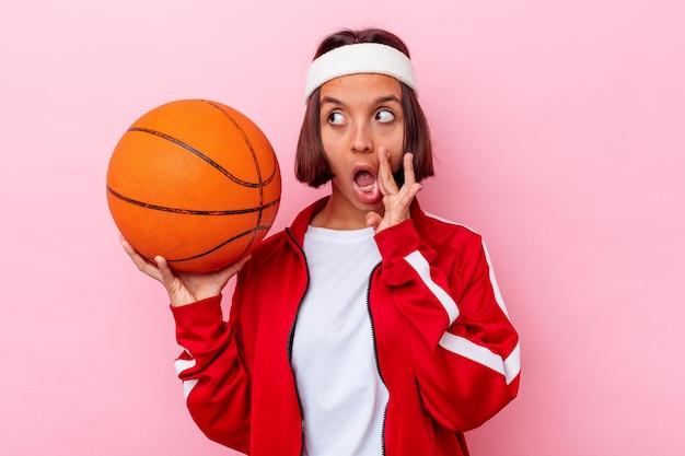 Junge mischlingsfrau, die basketball spielt, der auf rosa wand isoliert wird, sagt eine geheime heiße bremsnachricht und schaut beiseite