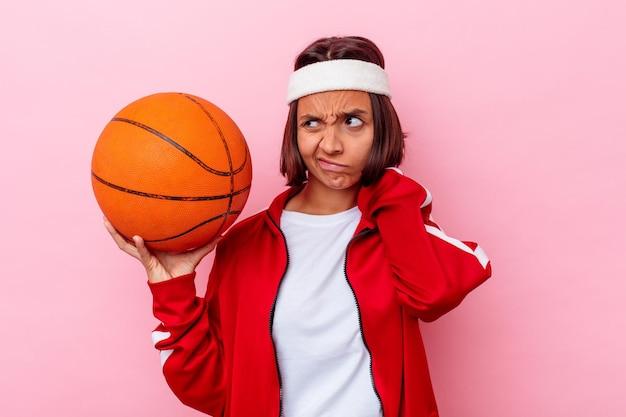 Junge mischlingsfrau, die basketball spielt, isoliert auf rosa wand, die hinterkopf berührt, denkt und eine wahl trifft.