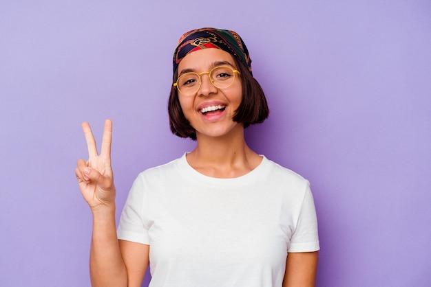 Junge mischlingsfrau, die ein bandana trägt, das auf purpurrotem hintergrund isoliert ist und die nummer zwei mit den fingern zeigt.