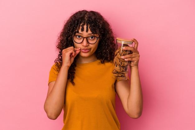 Junge mischlingsfrau, die ein keksglas auf rosafarbenem hintergrund mit fingern auf den lippen hält, die ein geheimnis halten.