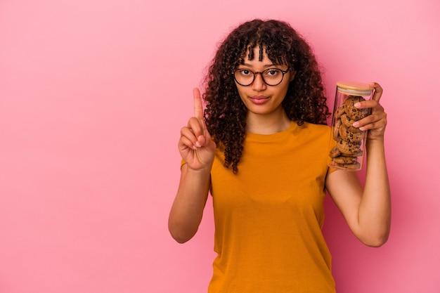 Junge mischlingsfrau, die ein keksglas hält, das auf rosa hintergrund isoliert ist und die nummer eins mit dem finger zeigt.