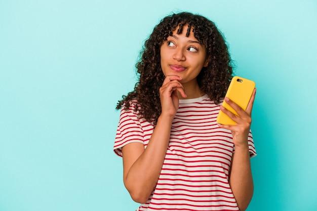 Junge mischlingsfrau, die ein mobiltelefon einzeln auf blauem hintergrund hält und seitlich mit zweifelhaftem und skeptischem ausdruck schaut