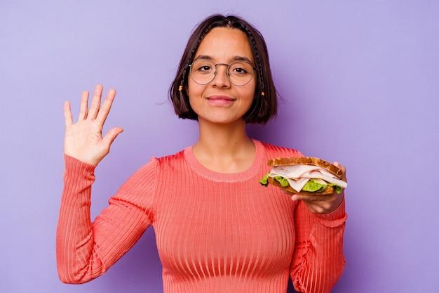 Junge mischlingsfrau, die ein sandwich auf violettem hintergrund isoliert hält, lächelt fröhlich und zeigt nummer fünf mit den fingern