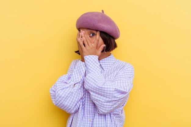 Junge mischlingsfrau, die eine baskenmütze trägt, die auf gelbem hintergrund lokalisiert wird, blinzelt durch erschrockene und nervöse finger.