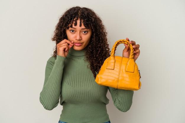 Junge mischlingsfrau, die eine handtasche lokalisiert auf weißem hintergrund mit den fingern auf den lippen hält, die ein geheimnis halten.