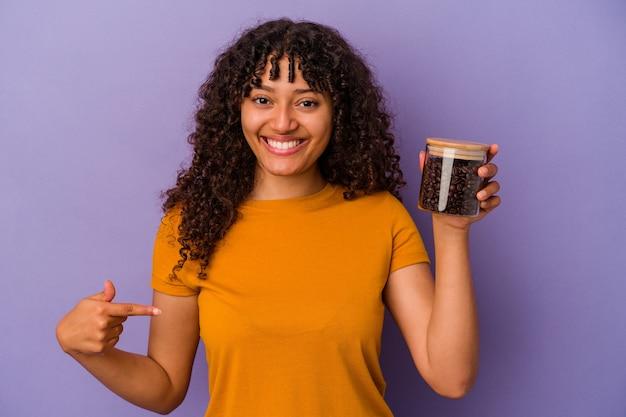 Junge mischlingsfrau, die eine kaffeebohnenflasche einzeln auf violettem hintergrund hält