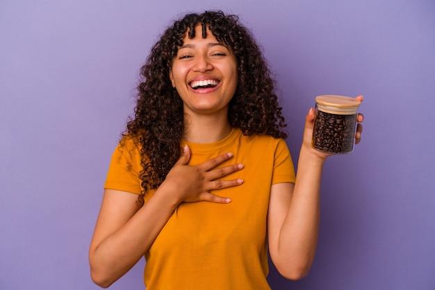 Junge mischlingsfrau, die eine kaffeebohnenflasche lokalisiert auf lila wand hält, lacht laut und hält hand auf brust.