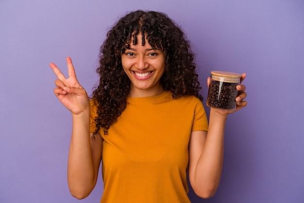 Junge mischlingsfrau, die eine kaffeebohnenflasche lokalisiert auf violettem hintergrund hält, die nummer zwei mit den fingern zeigt.