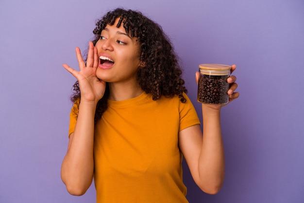 Junge mischlingsfrau, die eine kaffeebohnenflasche lokalisiert auf violettem hintergrund hält, die palme nahe geöffnetem mund schreit und hält.