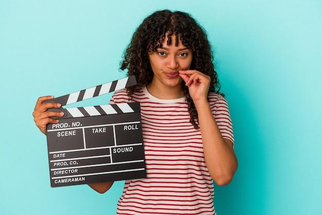 Junge mischlingsfrau, die eine klappe auf blauem hintergrund mit fingern auf den lippen hält, die ein geheimnis halten.