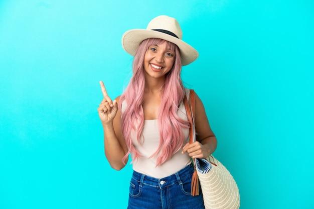 Junge mischlingsfrau, die eine strandtasche mit pamela hält, die auf blauem hintergrund isoliert ist, zeigt und hebt einen finger im zeichen des besten