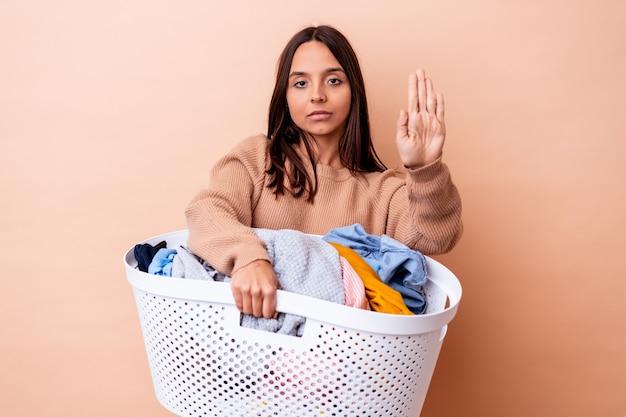 Junge mischlingsfrau, die eine wäsche isoliert hält, die mit ausgestreckter hand steht, die stoppschild zeigt, das sie verhindert.