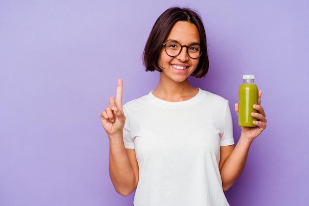 Junge mischlingsfrau, die einen gesunden smoothie hält, der auf purpurrotem hintergrund lokalisiert wird, der nummer eins mit dem finger zeigt.
