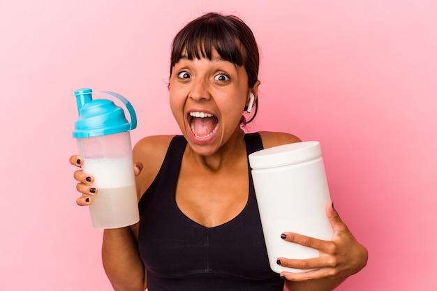Junge mischlingsfrau, die einen proteinshake trinkt, isoliert auf rosa hintergrund