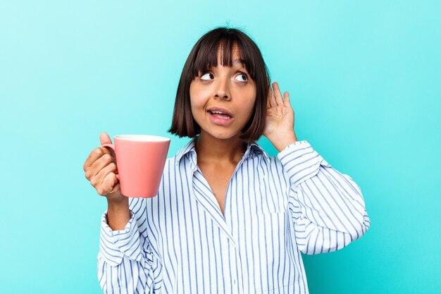 Junge mischlingsfrau, die einen rosa becher auf blauem hintergrund isoliert hält und versucht, einen klatsch zu hören.