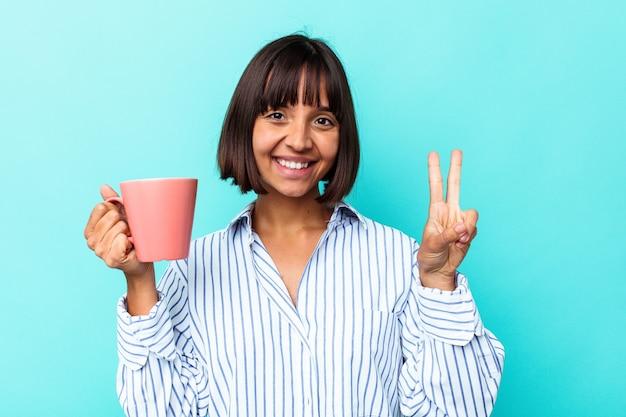 Junge mischlingsfrau, die einen rosa becher hält, der auf blauem hintergrund isoliert ist und nummer zwei mit den fingern zeigt.