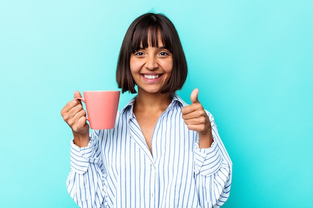 Junge mischlingsfrau, die einen rosa becher lokalisiert auf blauem hintergrund hält, lächelt und daumen hoch