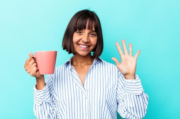 Junge mischlingsfrau, die einen rosafarbenen becher lokalisiert auf blauem hintergrund hält, der fröhlich lächelt und nummer fünf mit den fingern zeigt.